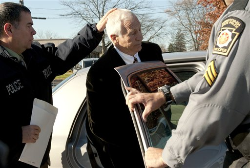 Former Penn State football defensive coordinator Gerald &quotJerry&quot Sandusky is placed in a police car iin Bellefonte, Pa., to be taken to the office of a Centre County Magisterial District judge on Saturday, Nov. 5, 2011.