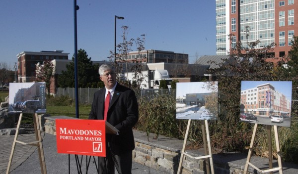 Nicholas Mavodones uses pictures and the backdrop of Bayside neighborhood commercial development to illustrate how Portland has attracted investment during his tenure on the City Council and as mayor. Mavodones is running to be popularly elected as mayor of the city on Nov. 8 as the position changes from being chosen by his fellow city councilors to being elected by voters.