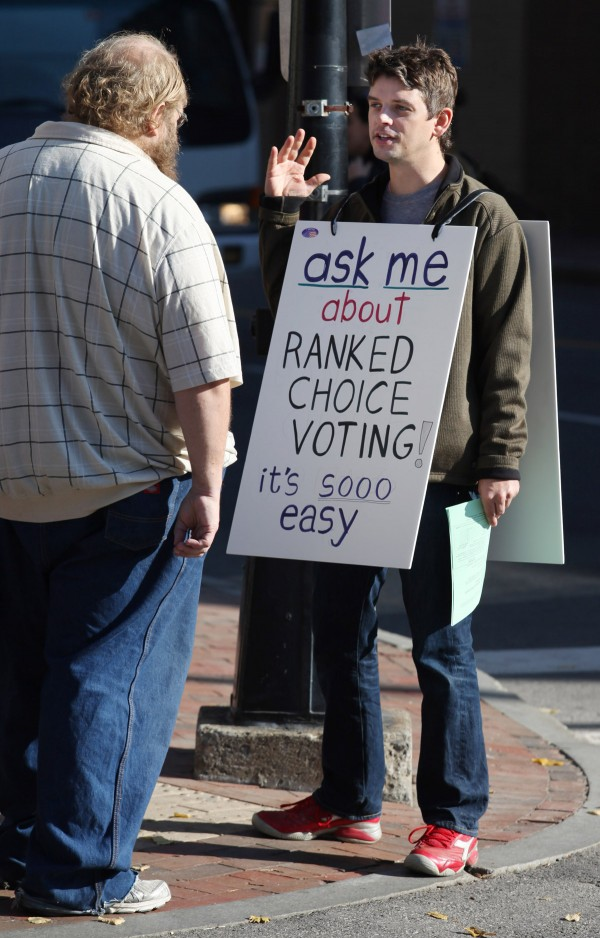 Carlin Whitehouse, of the League of Young Voters (right) speaks with Nicholas Elby (left) about Ranked Choice Voting, Tuesday, Nov. 8, 2011 in Portland, Maine.