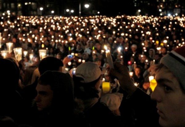 Students hold candles during a vigil in front of the Old Main building on the Penn State Campus Friday in State College, Pa. The vigil is being held in support of the alleged victims of a child sex abuse scandal involving a former assistant coach.