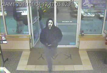 An image from the jewelry store camera shows a masked robber entering the store.