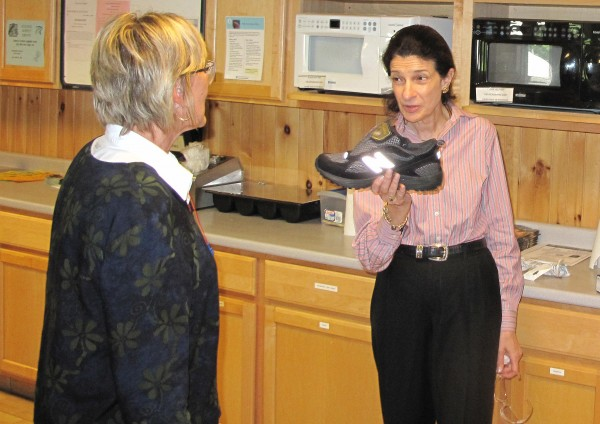 U.S. Sen. Olympia Snowe holds a New Balance shoe as she talks with an employee during a tour of the New Balance factory in Norridgewock in August, 2011.