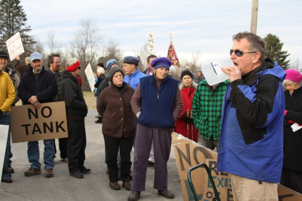 Randall Parr, 67, of Appleton, shouted through half a milk gallon to a crowd of protesters. About 100 people gathered in Searsport on Saturday to rally against a plan to build a large propane storage tank in town.