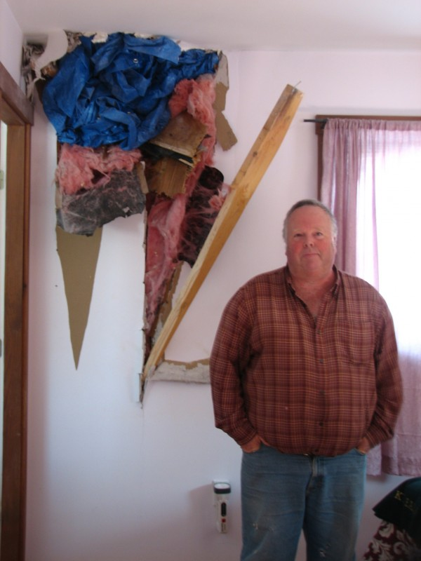 Tremont resident Bruce Rich stands next to a hole Friday, Nov. 25, 2011, in his bedroom where a rock thought to be the size of a basketball blasted through the wall of his Spruce Lane home.