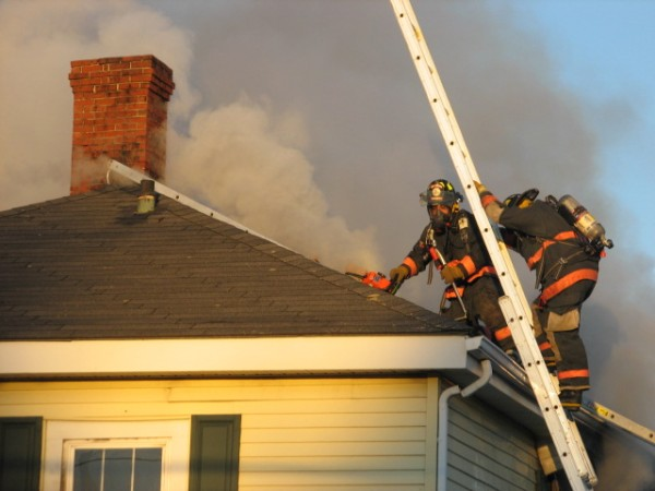 Firefighters use a chainsaw to cut through the roof of a house at 1172 Bar Harbor Road in Trenton on Wednesday afternoon after a grease fire spread throughout the house around 4 p.m. No one was injured in the blaze, which resulted in the highway being close to traffic for more than an hour, according to Trenton Fire Chief Richard Gray.