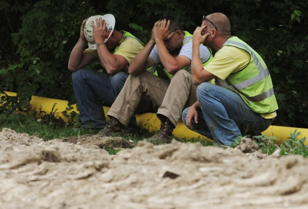 Construction wokers sit silently with their heads in their hands as police and fire officials inspect an excavator that rolled over and killed a worker along Odlin Road in Bangor on Wednesday, July 27, 2011.