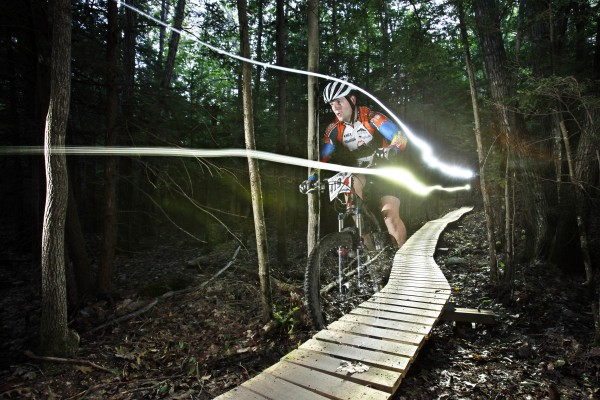 A headlamp and bike light leave trails in a time exposure of Sean Savignano of Auburn as he cruises down a boardwalk in the dark on the last lap of the 12 Hours of Bradbury Mountain bike race in September.