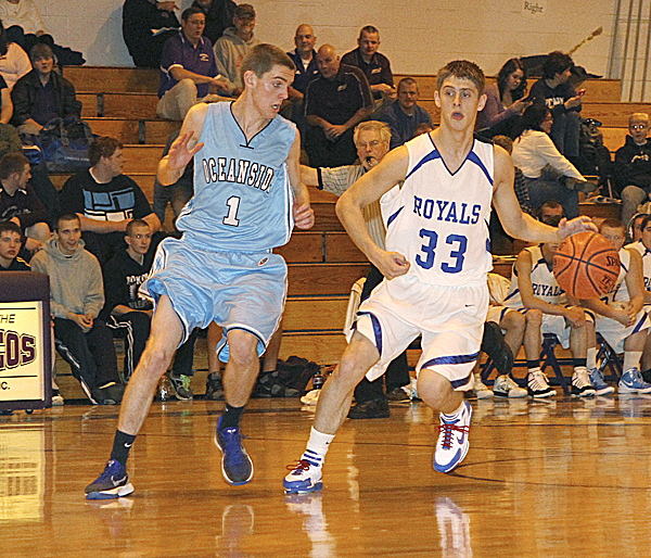 Jonesport-Beals' Matt Alley brings the ball up the court while guarded by Oceanside's Ben Wallace during an exhibition game played at Hampden on Saturday, Nov. 26. The high school basketball season opens Dec. 9.