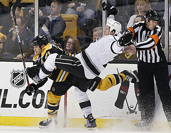 Los Angeles Kings center Colin Fraser (24) goes flying after colliding with Boston Bruins defenseman Andrew Ference (21) as referee Dave Jackson (8) protects himself in the second period of an NHL hockey game in Boston Tuesday night, Dec. 13, 2011.