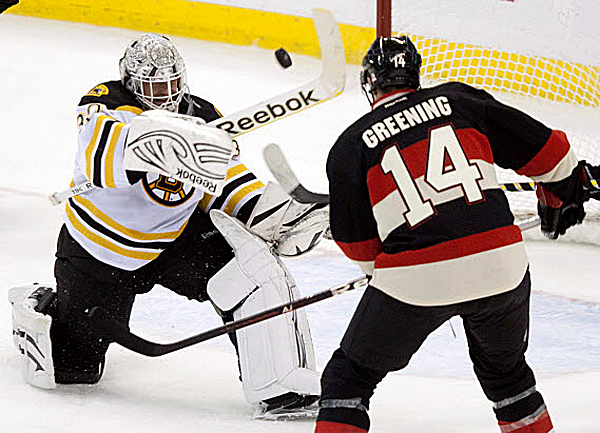 Boston Bruins goalie Tim Thomas, left, swings his stick to clear an airborne puck as he is pressured by Ottawa Senators left wing Colin Greening during the second period of Wednesday's NHL hockey game action in Ottawa, Ontario. The Bruins won 5-2.