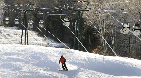 In this photo taken Monday Dec. 12, 2011, empty gondolas sit parked above a lone skier on an open trail at Loon Mountain ski area in Lincoln, N.H.  Warm temperatures have continued to hover above optimal snowmaking levels, making for a late start to the ski season in the Northeast.