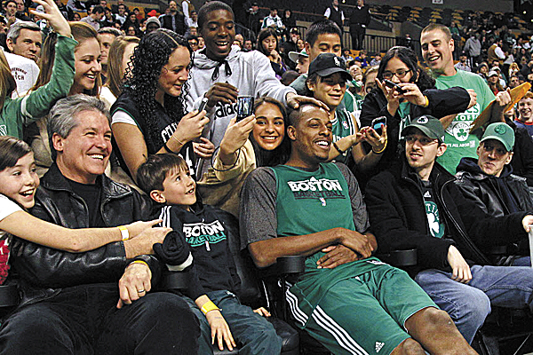 Boston Celtics forward Paul Pierce sits with fans as his teammates warm up at an NBA practice prior to a scrimmage in Boston, Friday Dec. 16, 2011. Pierce did not participate in the practice or scrimmage.