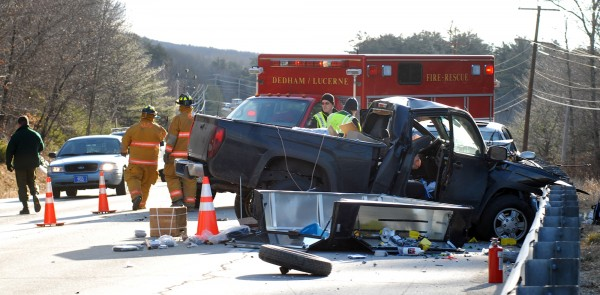 Police and fire personnel work at the scene of a head-on collision that resulted in one fatality Tuesday morning on Route 1A in Dedham.