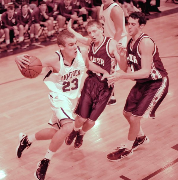 Hampden Academy player Zachary Gilpin (23) drives the baseline on Bangor's John Szewczyk (12) and Robbie Brookings (34) in the first half of their game in Hampden on Friday, Dec. 9, 2011.