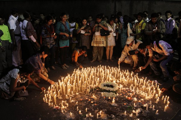 People light candles at a crossing near the AMRI Hospital in memory of those who died in Friday's fire, in Kolkata, India, Monday, Dec. 12, 2011. The top official in India's West Bengal state told mourners Monday that her government was working to ensure that the hospital fire would be the last tragedy of its kind. Officials say lax safety standards contributed to the tragedy where much of the staff fled, leaving patients to suffocate from smoke inhalation from the basement fire.