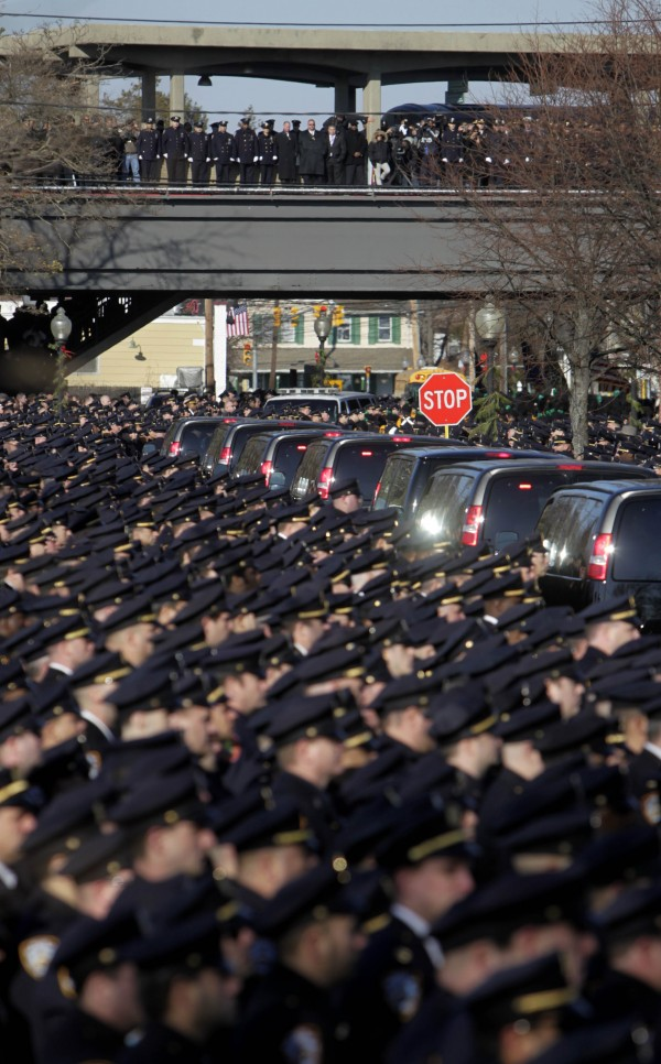 Police officers fill the the streets and an elevated Long Island Railroad station as the funeral procession for New York Police Department Officer Peter Figoski passes by in Babylon, N.Y., Monday, Dec. 19, 2011. Thousands of officers from police departments around New York state gathered Monday to remember Figoski, who was shot to death during a botched robbery in Brooklyn on Dec. 12.