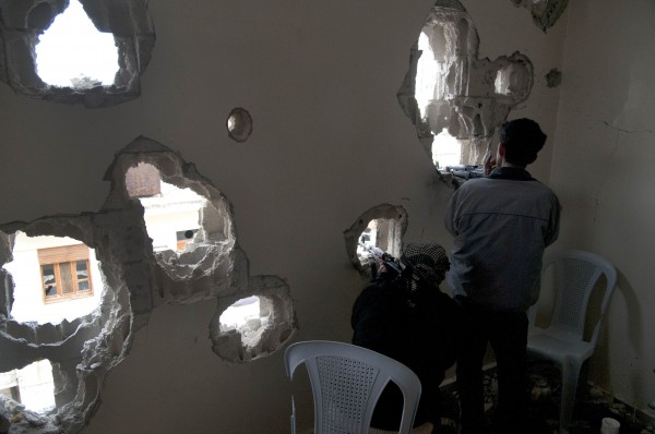 Defected Syrian soldiers position their rifles as they take cover behind a the wall of a damaged house in the Baba Amr area, in Homs province, Syria, on Monday, Dec. 19, 2011.