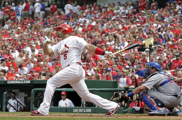 St. Louis Cardinals first baseman Albert Pujols (5) follows through on a solo home run as Chicago Cubs catcher Geovany Soto watches in the first inning of a baseball game, in St. Louis on July 30, 2011.