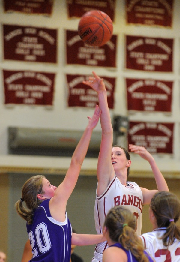 Bangor High School's Katie Brochu (right) makes a shot over Hampden Academy's Helene Sherburne during the first half of the game in Bangor on Friday evening.
