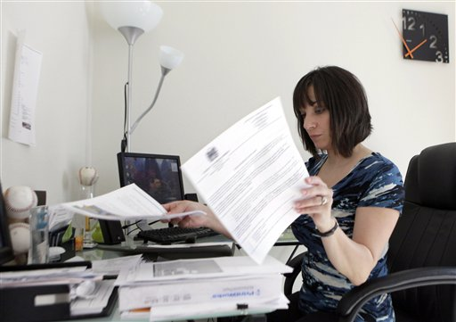 In this Nov. 10, 2010 photo, Gina Marie Haynes looks over documents before heading to a job interview in Frisco, Texas. Gina Marie Haynes had just moved from Philadelphia to Texas with her boyfriend in August 2010 and lined up a job managing apartments. A background check found fraud charges, and Haynes lost the offer.