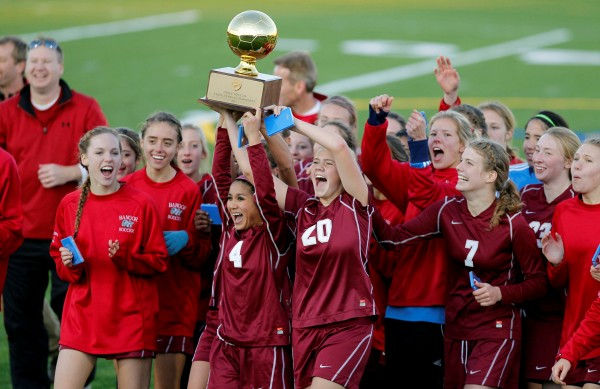 Bangor's Jade Baumrind (4) and Elizabeth Hintz (20) lead their teammates in a celebration with the trophy after defeating Scarborough in the Class A soccer state championship in Falmouth on Saturday, Nov. 5, 2011.