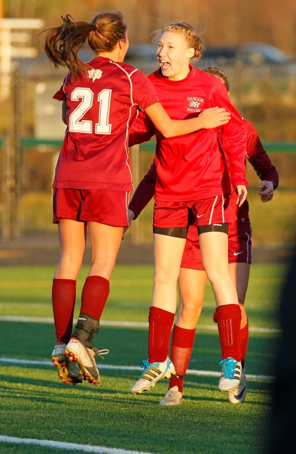 Bangor's Ashley Robinson (21) and Leanne Violette jump for joy after defeating Scarborough in the Class A soccer state championship in Falmouth on Saturday, Nov. 5, 2011.