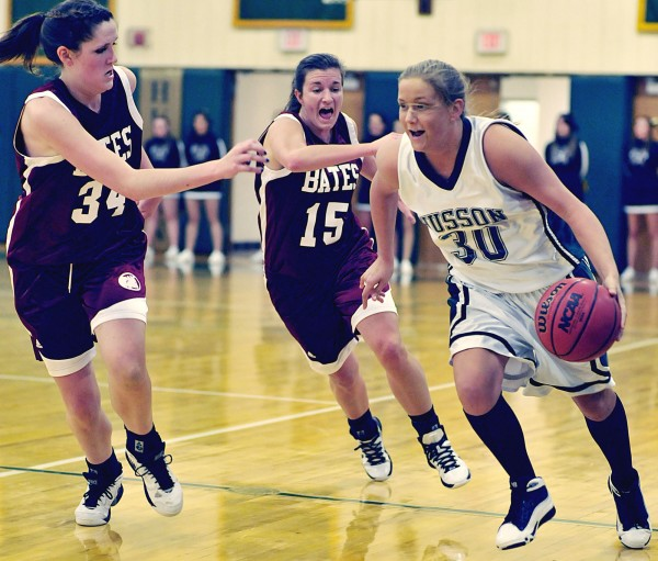 Kelli Murray (30) of Husson University breaks defensive pressure from Jessie Igoe (34) and Kelsey Flaherty (15) of Bates College during a game last season. Murray has helped lead Husson to a 3-4 start this season by averaging 11.4 points and 6.3 rebounds a game.