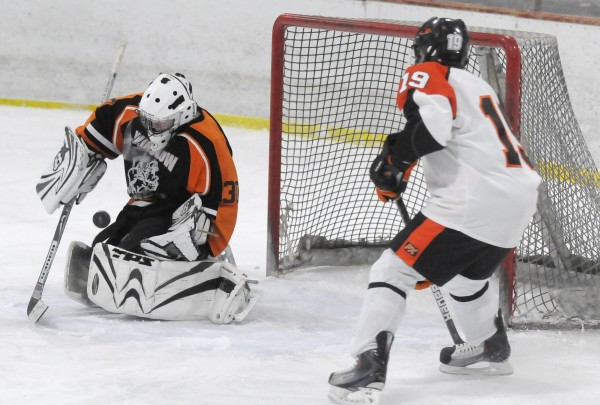 Winslow High School goaltender Cameron Tibbetts deflects a score attempt from Brewer High School's Kyle Alexander in the third period of their game at Penobscot Ice Arena in Brewer on Tuesday afternoon, Dec. 20, 2011. Brewer defeated Winslow 7-1.