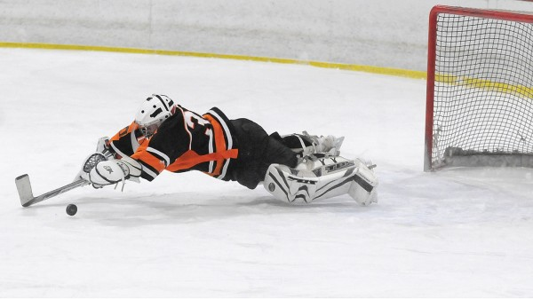 Winslow High School goaltender Cameron Tibbetts lunges to make a save on a Brewer goal attempt in the third period of their game at Penobscot Ice Arena in Brewer on Tuesday afternoon, Dec. 20, 2011. Brewer defeated Winslow 7-1.