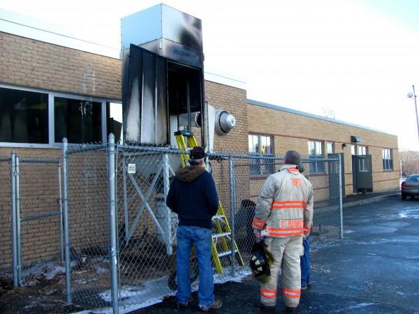 Bucksport Fire Department Chief Craig Bowden (center) examines a dust collection unit that caught fire on Thursday, Dec. 22, 2011, outside of the wood shop at Bucksport High School.