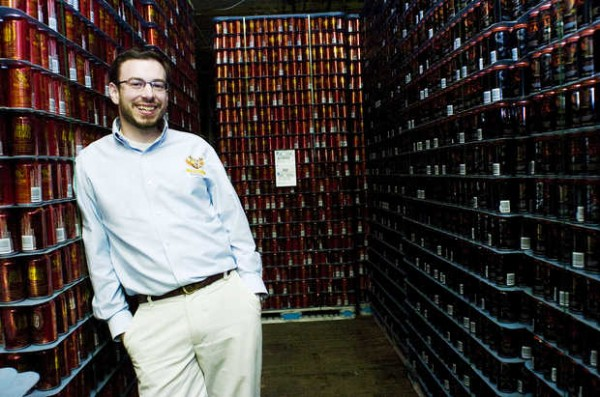 Baxter Brewing founder Luke Livingston poses with cans waiting to be filled with the company's craft beers in the Bates Mills brewery. Livingston was named one of the 30 most influential people under the age of 30 in the food and wine category by Forbes Magazine on Monday.