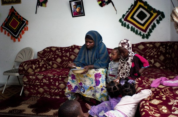 Ghali Farah (center) tries to get a moment for herself to eat lunch while baby-sitting other Somali parents' children. Farah is one of many women who earn income by providing informal child care for working parents, often watching more than a dozen children at a time.