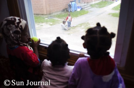 Somali girls watch young boys playing outside at the Hillview housing complex. Conservative Somali gender roles have perplexed some Lewiston residents.