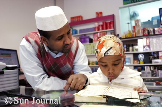 Hussein Ahmed helps his daughter Hibo, 8, to read the Koran in Arabic at Ahmed's shop on Lisbon Street. Ahmed's four oldest children attend classes at the Islamic Center for several hours each Saturday and Sunday, learning about Islam and reciting from the Koran.