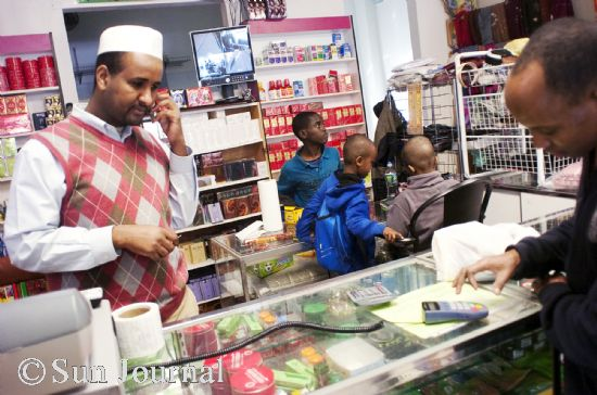 Hussein Ahmed (left) talks on the phone while ringing up a customer at his shop on Lisbon Street. Lewiston has come a long way since he moved here in 2002, he says, and he believes an even brighter future is in store as the city and its Somali and other immigrant populations increasingly work together.