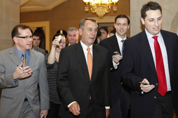Speaker of the House John Boehner of Ohio (center) is surrounded by reporters after leaving a House vote on the payroll tax cut in Washington, on Friday, Dec. 23, 2011.