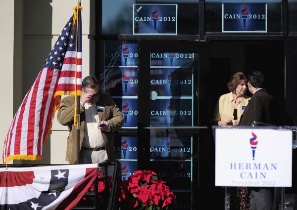 Michael Fitzgerald (left) campaign volunteer for Republican presidential candidate Herman Cain, waits for the start of an event for presidential candidate Herman Cain outside his new state headquarters Saturday, Dec. 3, 2011, in Atlanta, Ga.