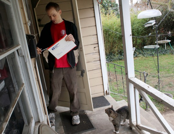 In this photo taken Dec. 15, 2011, Trent Arsenault receives a certified letter regarding his sperm donation to a potential parent at his home in Fremont, Calif. Arsenault has fathered 14 children in the last five years through free sperm donations to childless couples he meets on the Internet.