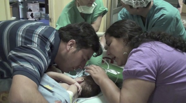 In this image taken from a video released by Luis Calvo Mackenna Hospital, Jessica Navarrete, right, and Roberto Paredes, parents of conjoined twins Maria Paz and Maria Jose Paredes Navarrete kiss them before a separation surgery in Santiago, Chile, Tuesday, Dec. 13, 2011. Maria Jose did not survive the operation, and Maria Paz remains clinging to life.
