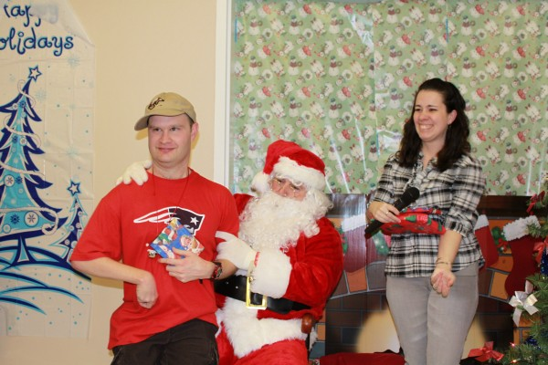 Michael Petros receives a gift from Santa, aka Ken Bustard, during the Downeast Horizons Christmas Party on Thursday at the MDI Shelter in Bar Harbor. Helping Santa is Tiffany Sargent, a staffer with the organization, which provides services to adults and children with developmental disabilities in Hancock, Penobscot, Piscataquis and Waldo counties.
