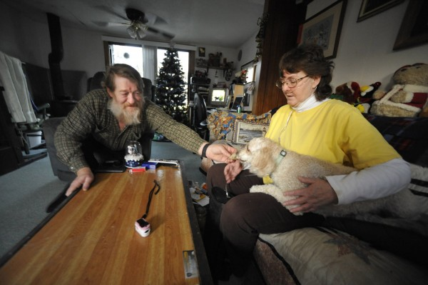 Janet Bouchard (right) and her boyfriend Jack McCoy (left) spend some quality time with their four-year-old poodle Mason Bailey at their home in Orland Monday, Dec. 12, 2011.