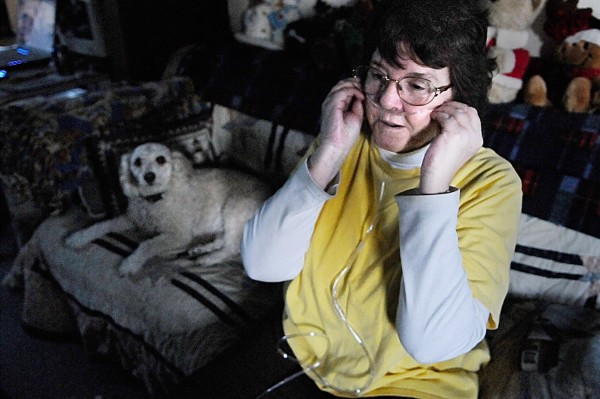 Janet Bouchard adjusts her oxygen tubing from a portable oxygen tank at her home in Orland. Next to her is her four-year-old poodle Mason Bailey.