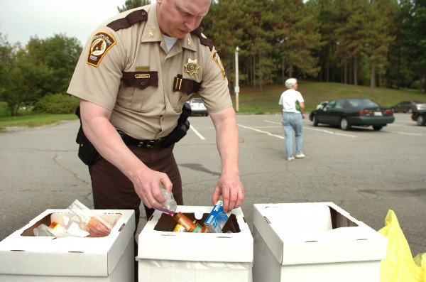 Chief Troy Morton with the Penobscot County Sheriff's Department dispenses drugs into containers which were turned in by community members as part of a national prescription drug take-back campaign at Cascade Park in Bangor in September 2010.