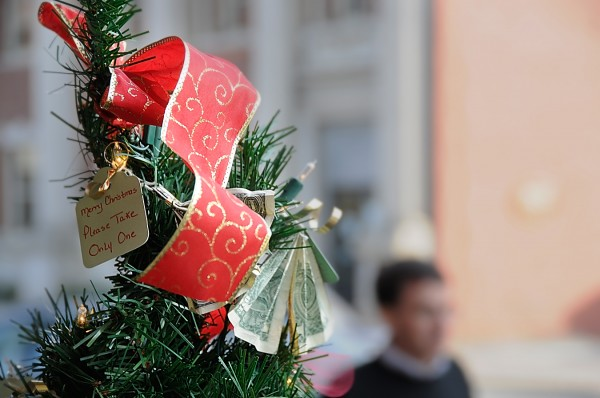 "Dollar donations are clipped to a small holiday ""Giving Tree"" in downtown Bangor Tuesday Dec. 14, 2011."