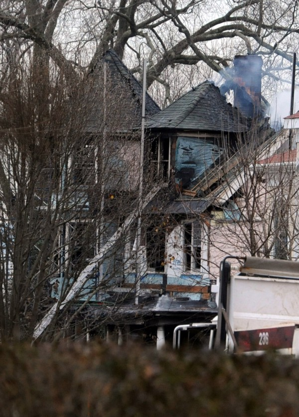 Smoke still rises from a house fire in Stamford, Conn., Sunday, Dec. 25, 2011. According to a brief statement by Mayor Pavia, the fire claimed the lives of five people, including three children.