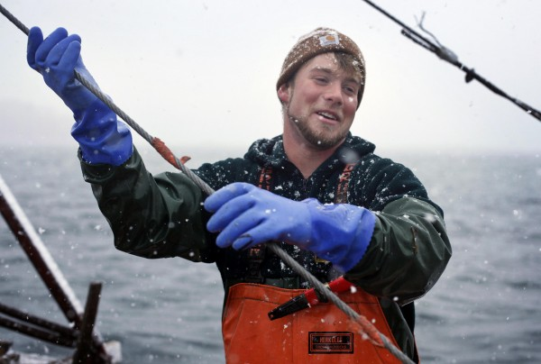 Scallop fisherman Josh Gatto guides a cable as the dragger is hauled in in the waters off Harpswell on Saturday, Dec. 17, 2011. The scallop fishing season opened on Dec. 17 and runs through March.