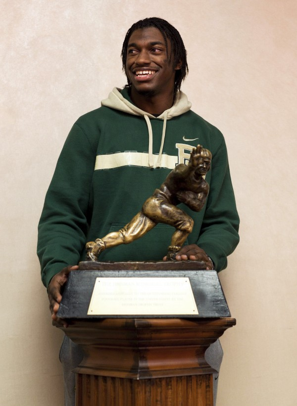 Baylor quarterback and Heisman Trophy finalist Robert Griffin III stands with the trophy after an informal roundtable conference with media members, Friday, Dec. 9, 2011, in New York.