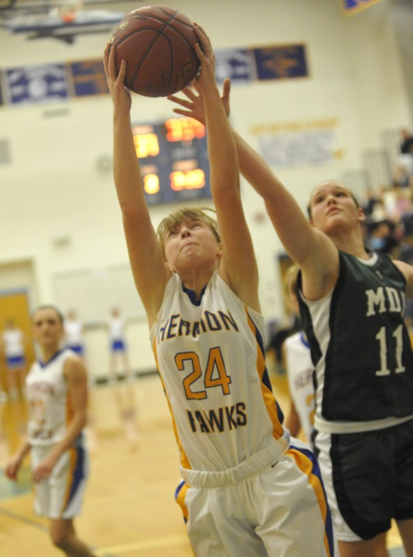 Hermon's Jenna Crouse (24) and MDI's Abby Jewett (11) go up for a rebound under the bucket  during the third period of their basketball game at Hermon High School on Tuesday night, Dec. 27, 2011.