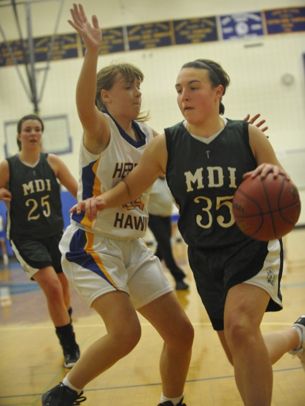 MDI's Sara Norberg (35) works around Hermon's Jenna Crouse on her way to the hoop in the third period of their basketball game at Hermon High School on Tuesday night, Dec. 27, 2011. In the background, on left, is MDI's Hannah Shaw (25).