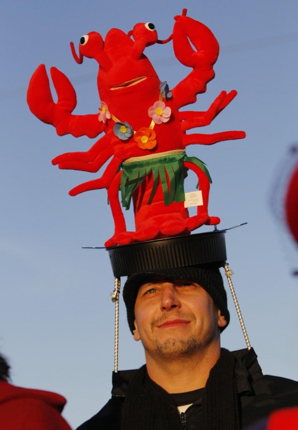 Adam Dorey of Lawrence, Mass., uses elastic cords to hold his lobster hat in place during last Saturday's Hat Parade.